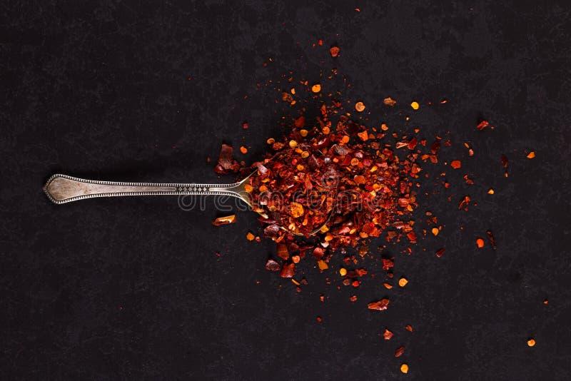 Crushgetrocknete Chili-Paprika in einem eisernen Löffel auf schwarzem Hintergrund Konzept, Kopierraum stockbild