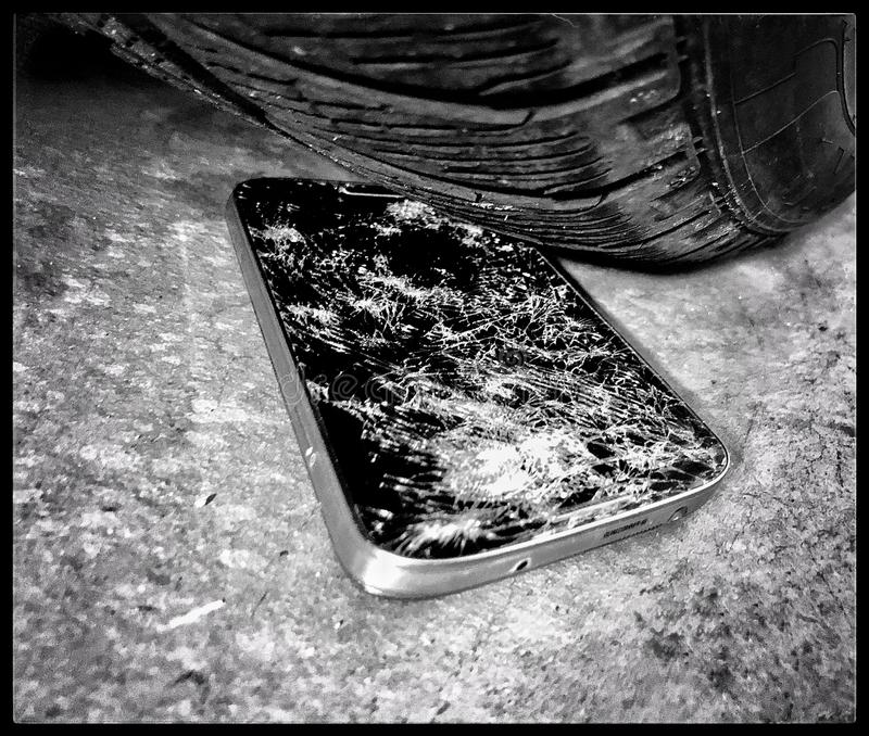 Crushing a smartphone with car tire. Crush tested smartphone, broken technology, non-functionality royalty free stock images