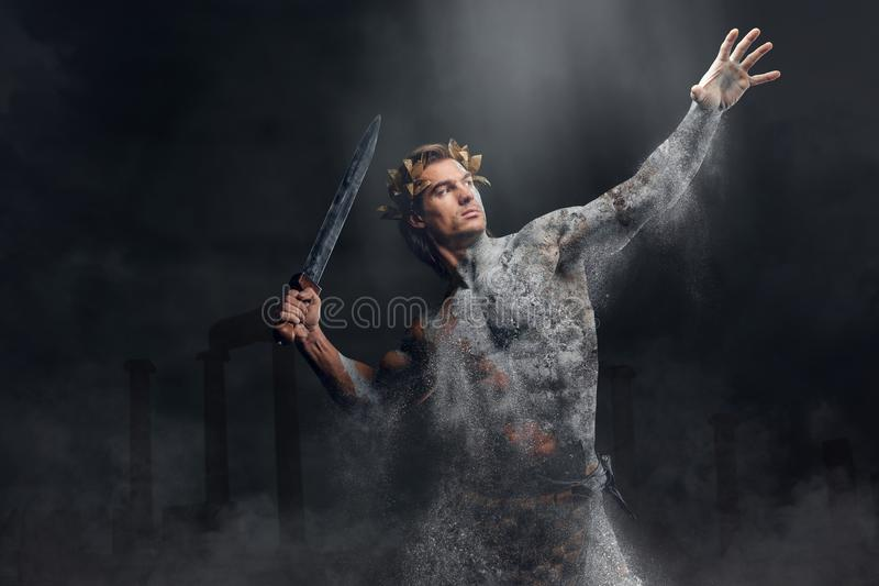 Crushing stone human athlete holds sword. royalty free stock photography