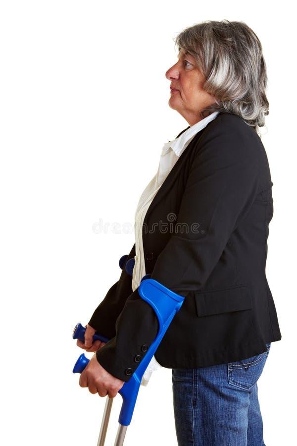 crutches пожилые люди используя женщину стоковое фото rf