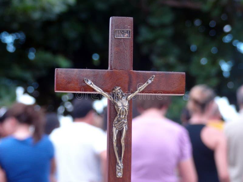 Cruxifix und Leute auf dem Hintergrund lizenzfreie stockfotografie