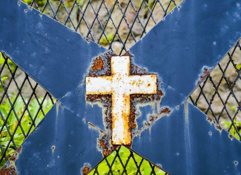 Cruz blanca oxidada en la cerca de acero imagen de archivo libre de regalías