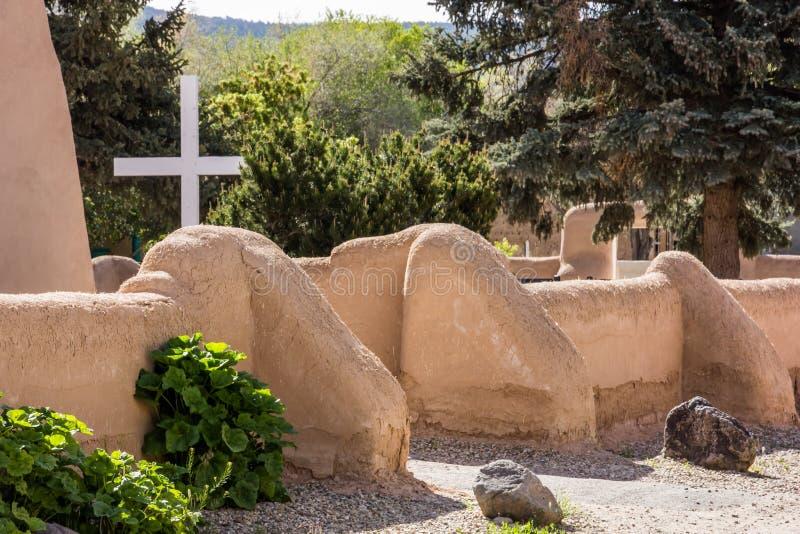Cruz blanca simple detrás de una pared de la iglesia del adobe foto de archivo libre de regalías