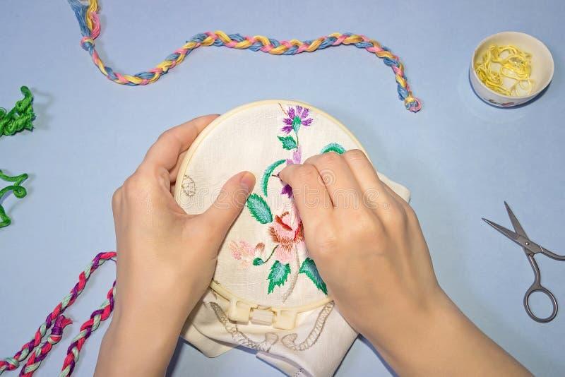 Cruz bordada mano femenina en la lona Algodón trenzado hilo en el fondo imagenes de archivo