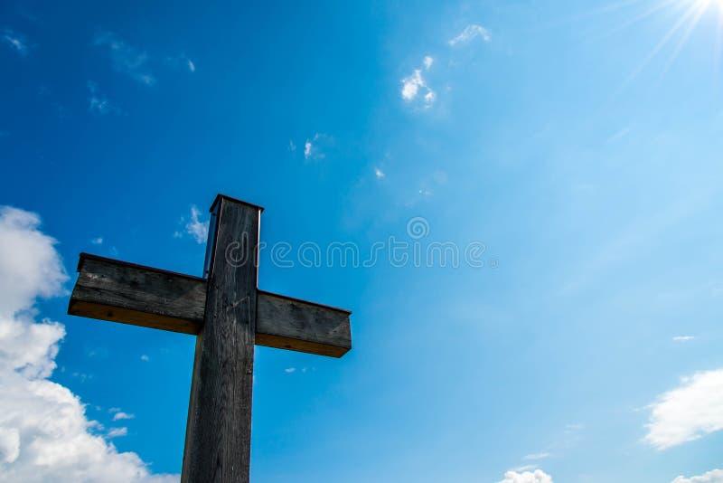 Cruz católica simples da madeira de carvalho, céu azul perfeito da luz solar visível fotografia de stock royalty free