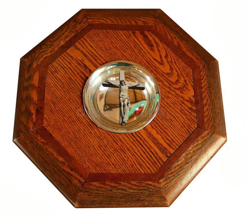Cruz com Jesus Christ na bacia de fonte batismal de madeira tradicional idosa com oito lados fotos de stock