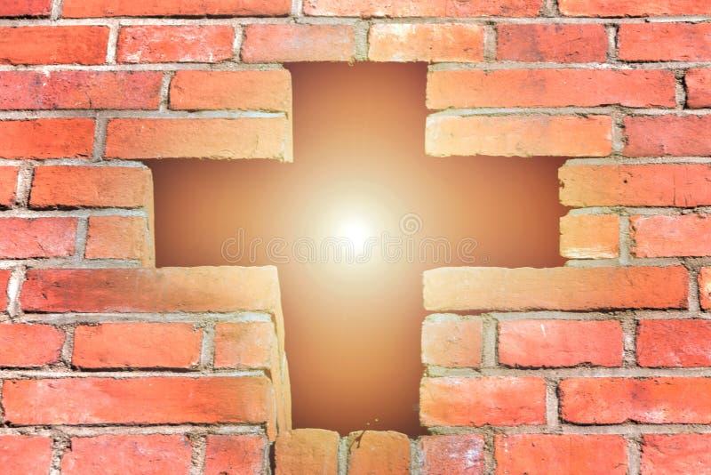 A cruz cristã feita dos tijolos, uma cruz brilhante está brilhando através do sol brilhante, fé no deus foto de stock