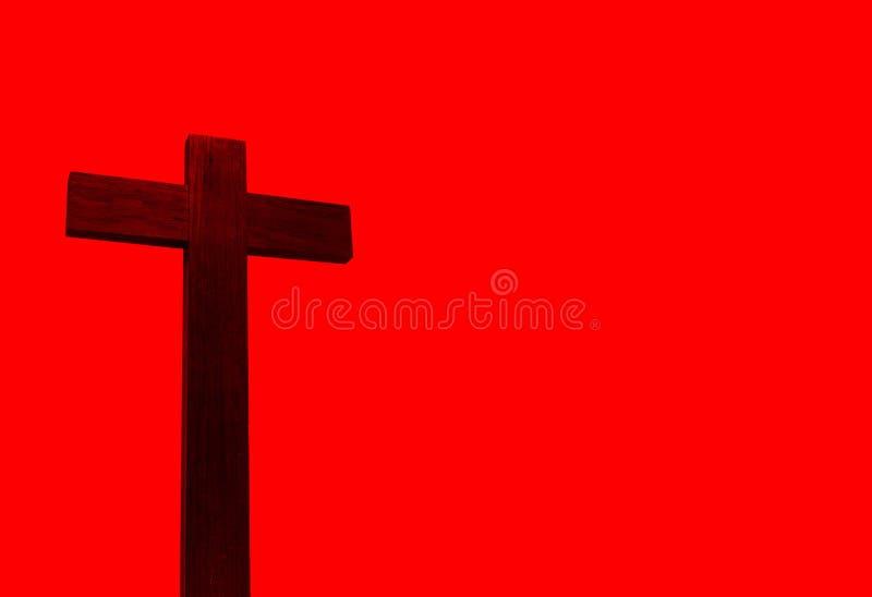Cruz cristiana aislada en fondo rojo fotos de archivo