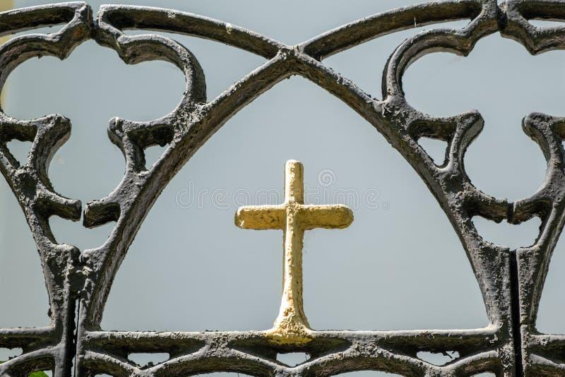 Cruz cristiana amarilla como parte de la cerca del metal fotos de archivo libres de regalías