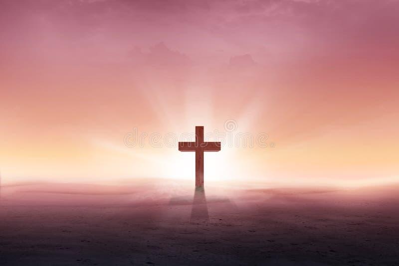 Cruz cristiana en el desierto con los rayos del sol foto de archivo