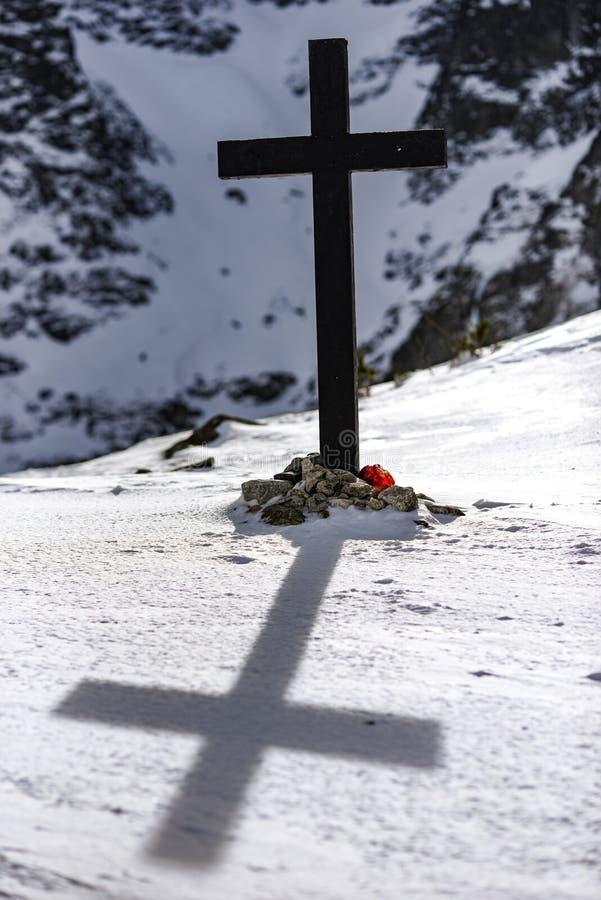 Cruz cristiana en las montañas del invierno Muerte en las montañas fotografía de archivo libre de regalías