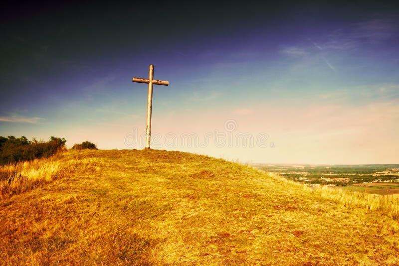 Cruz cristiana grande que se coloca encima de una colina Radobyl en área de CHKO Ceske Stredohori en la tarde en paisaje checo de foto de archivo