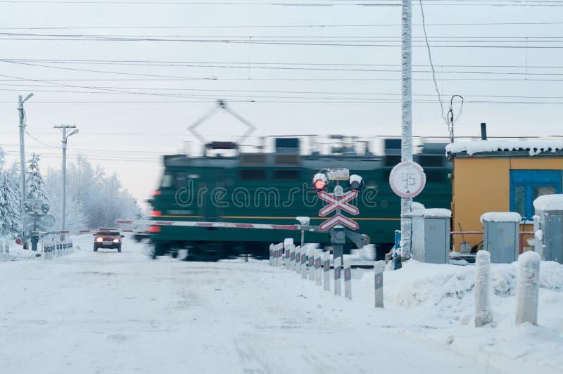 Cruz da categoria da estrada de ferro com passagem do trem, estação do inverno Condução de espera do carro imagem de stock royalty free