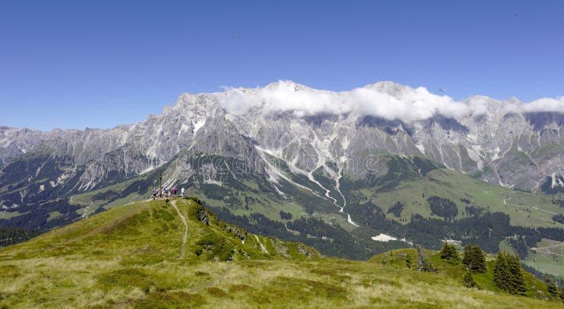 Cruz da montanha na frente da montanha de Hochkoenig fotos de stock
