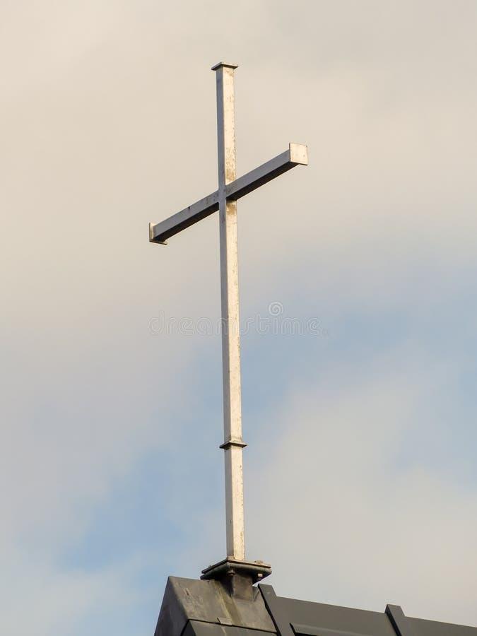 Cruz de acero encima del tejado de la iglesia imagenes de archivo