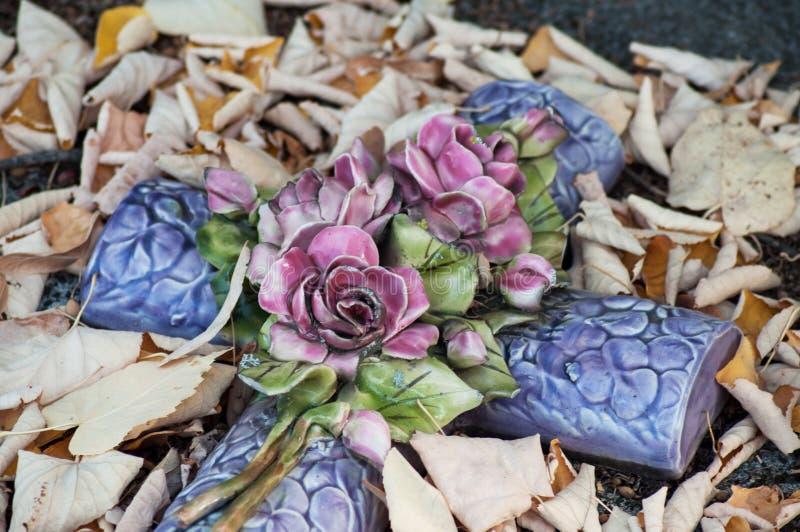 Cruz de cerámica en hojas muertas en la tumba en el cementerio foto de archivo