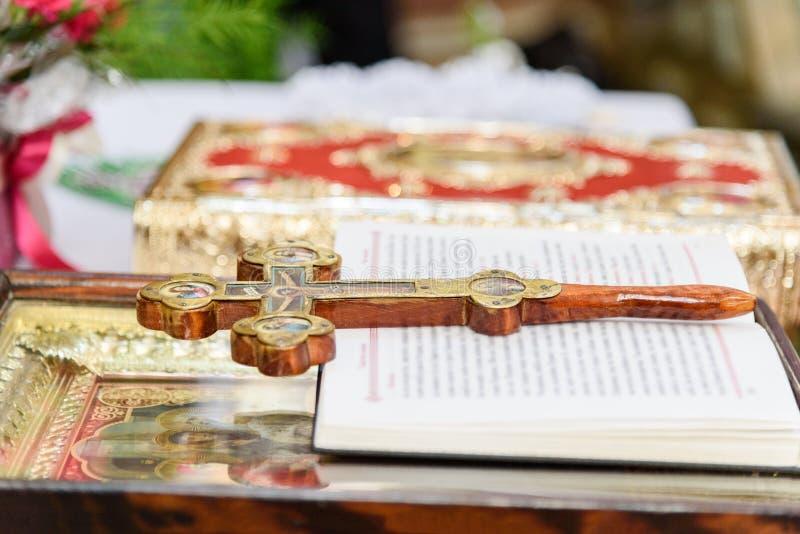 A cruz de madeira decorada, o livro de oração, o ícone e a Bíblia encontram-se no altar no templo cristão imagens de stock royalty free