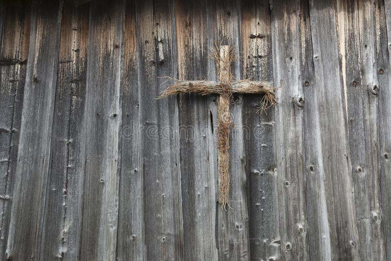 Cruz de madeira em uma parede de madeira fotografia de stock