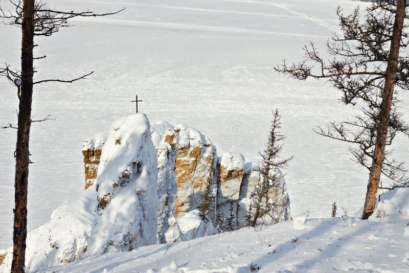 Cruz de madeira na rocha situada no banco de rio foto de stock royalty free