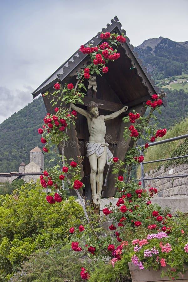 Cruz de madera con las rosas en el Tyrol del sur imagenes de archivo