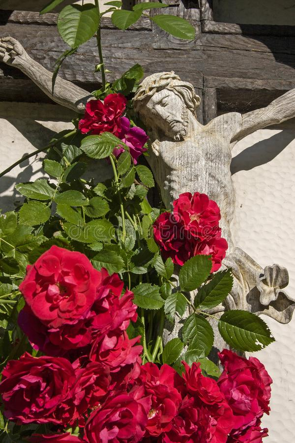 Cruz de madera con las rosas en el Tyrol del sur imagen de archivo libre de regalías