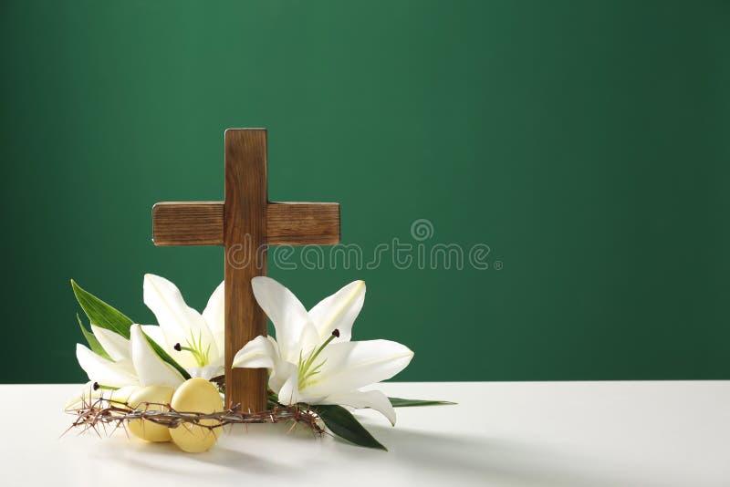 Cruz de madera, corona de espinas, de los huevos de Pascua y de los lirios del flor en la tabla contra fondo del color fotos de archivo libres de regalías