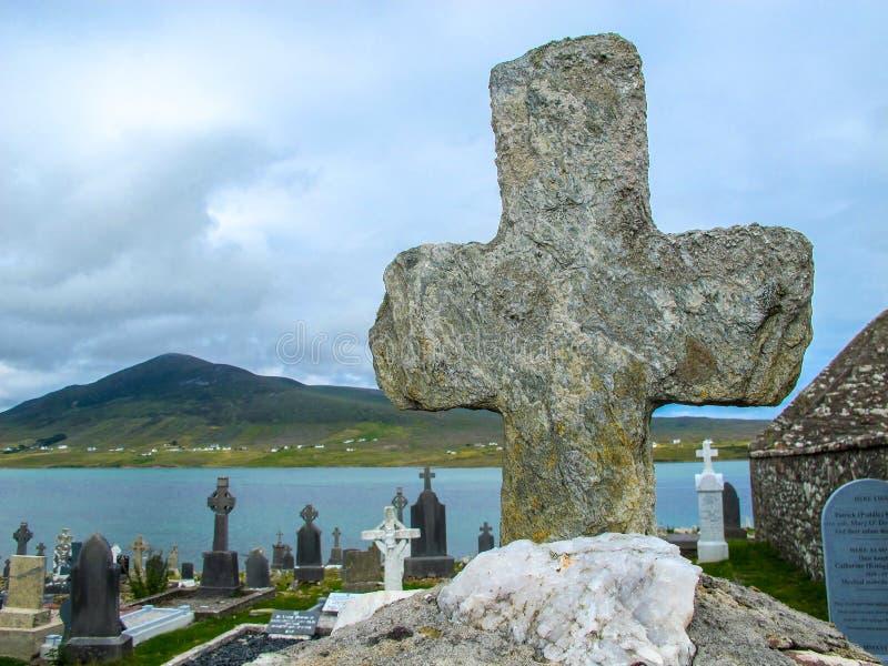 Cruz de pedra antiga que negligencia um cemitério muito rural foto de stock