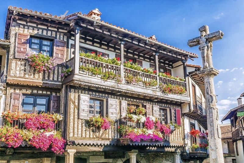 Cruz de pedra e arquitetura típica no quadrado principal do La Alberc imagem de stock