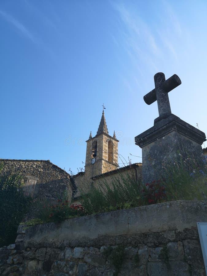 Cruz de pedra na frente de uma igreja velha fotos de stock