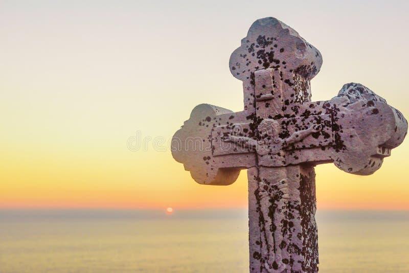Cruz de piedra con Jesús en ella en ocaso foto de archivo