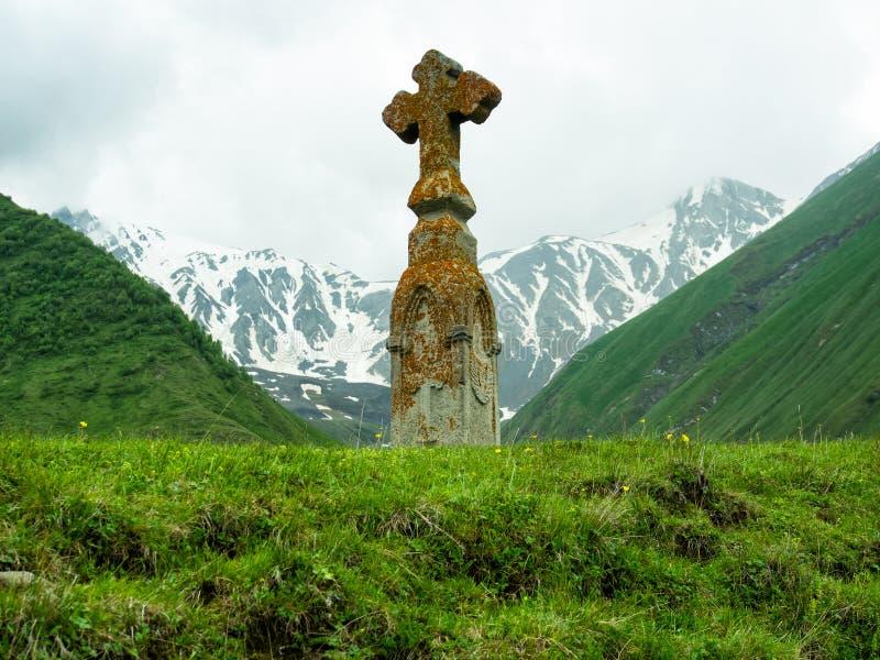 Cruz de piedra en el fondo de montañas nevosas imágenes de archivo libres de regalías