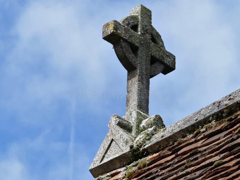 Cruz de piedra en tejado de la iglesia imagenes de archivo