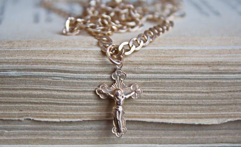 Cruz del oro con la cadena en un libro viejo imágenes de archivo libres de regalías