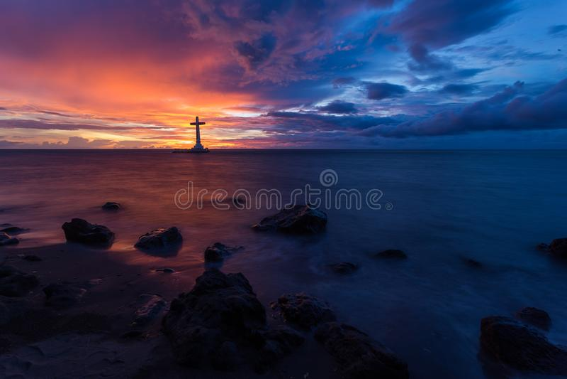 Cruz do por do sol e do cristão do mar fotografia de stock