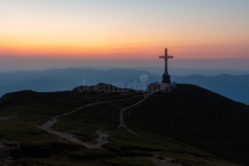 A cruz dos heróis no pico no alvorecer adiantado, montanhas de Caraiman de Bucegi, Romênia fotos de stock