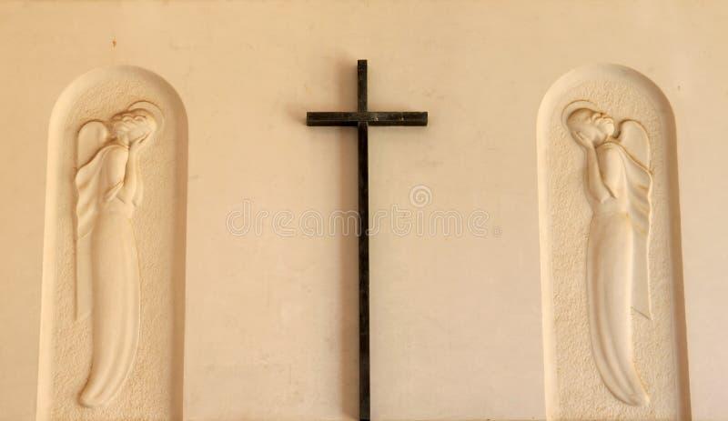Cruz e anjos no churchyard em Bruneck italiano fotografia de stock