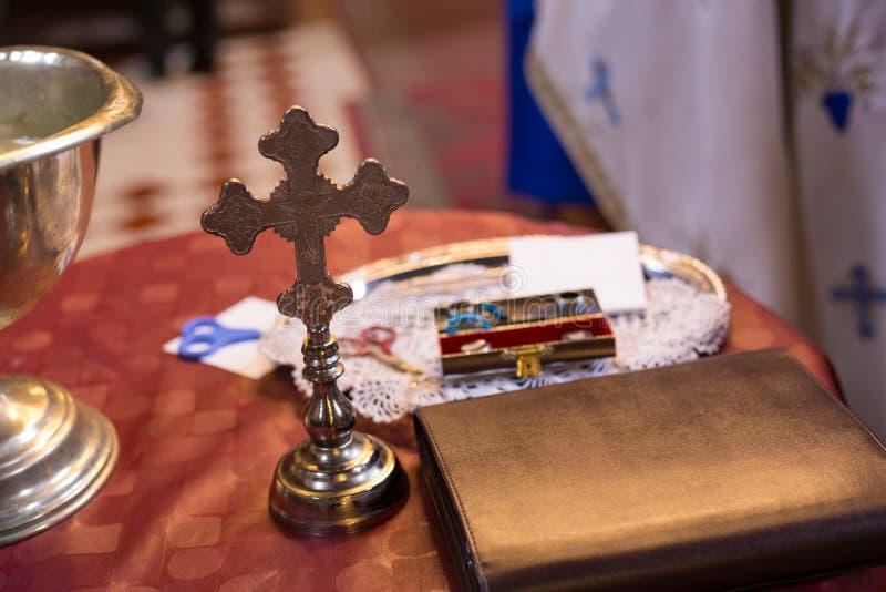 Cruz e a Bíblia isoladas na tabela Acess?rios do casamento da igreja ortodoxa imagem de stock royalty free