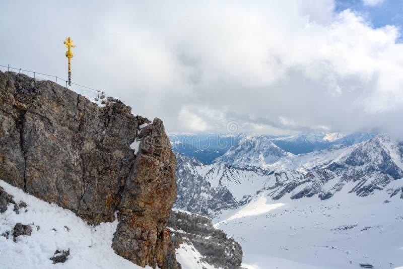 Cruz en el Zugspitze, la montaña más alta de la cumbre de Alemania en las montañas bávaras nevadas cerca de Garmisch Patenkir fotos de archivo libres de regalías