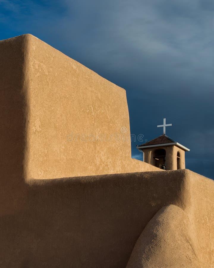 Cruz enmarcada por la pared grande del adobe imagenes de archivo