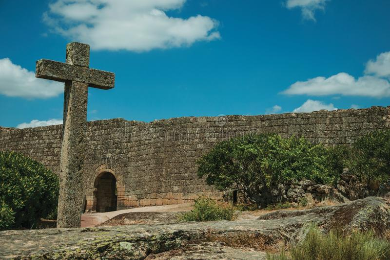 Cruz feita da pedra sobre o terreno rochoso e a grande parede fotografia de stock royalty free