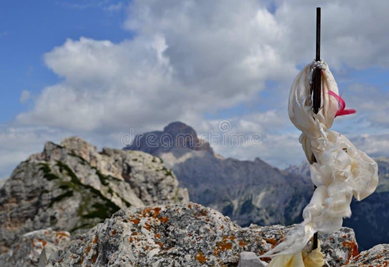 Cruz metálica con la bufanda blanca del lado en el top del pico de montaña - una serie de picos y de nubes de montaña está en el  imagenes de archivo