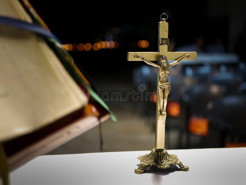 Cruz metálica puesta en un altar antes de una masa católica en la noche con el fondo borroso fotografía de archivo