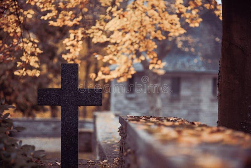 Cruz negra en el cementerio con el mausoleo fotos de archivo