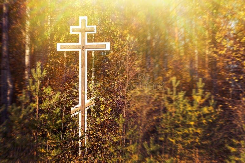 Cruz ortodoxa de la adoración en el bosque en el lado del camino en la entrada del pueblo en otoño foto de archivo