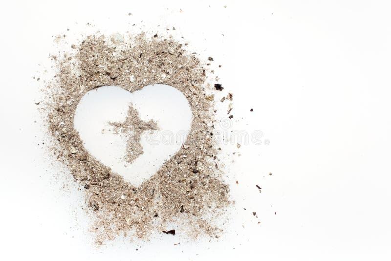 A cruz ou o crucifixo no símbolo do coração feito da cinza, emprestaram e conceitos de Ash Wednesday foto de stock