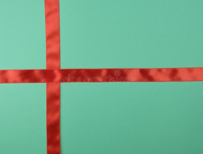 cruz roja de la cinta de satén a cruzar en fondo verde imagenes de archivo