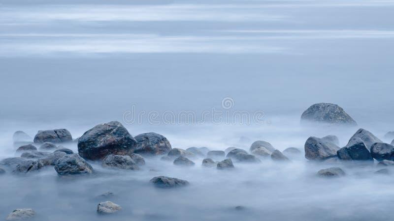 Cruz só na névoa em uma pilha de pedras molhadas imagem de stock royalty free