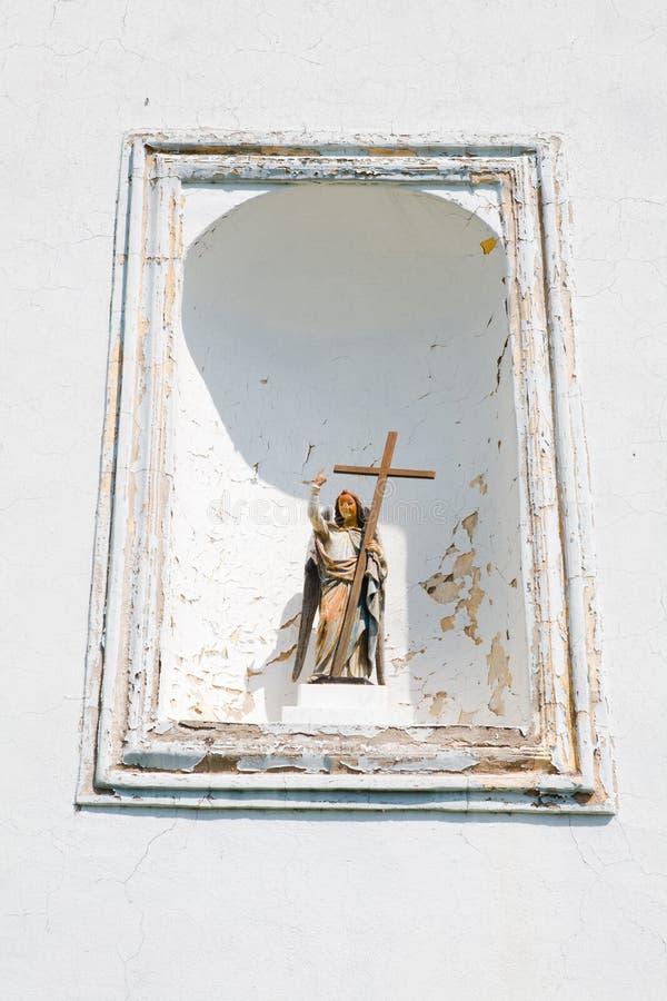 Cruz santamente da terra arrendada do anjo - ameia do vintage durante o dia ensolarado fotografia de stock royalty free