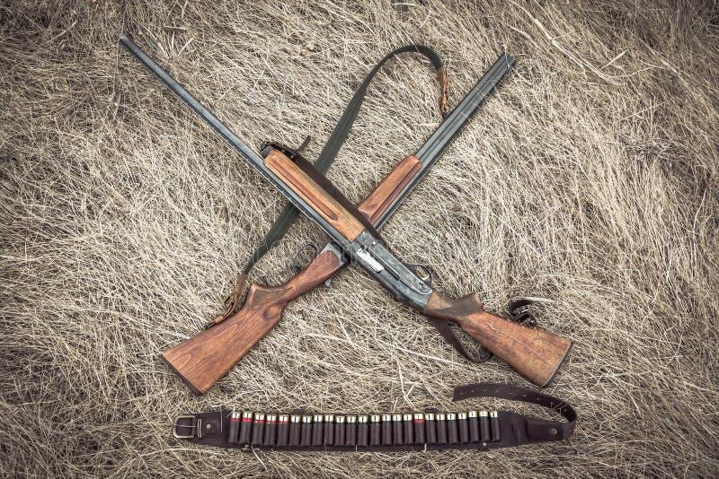 Cruzado cazando las escopetas con la correa de la munición en campo rural seco como fondo de la caza fotos de archivo