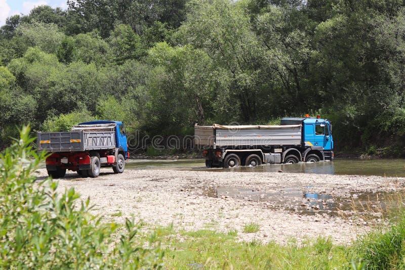 Cruzamento caminhões através de um rio raso da montanha Transporte dos bens em lugares difíciis de alcançar e em circunstâncias p imagem de stock
